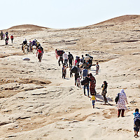 Dozens of Syrian refugees carrying luggage and children make their way from Syria into northern Iraq at a crossing near the town of Sahela outside of Dahouk in in Iraqi Kurdistan, Wednesday, August 28, 2013. Thousands of Syrian refugees have crossed into northern Iraq in the past week. August 2013.