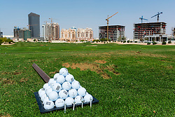 Skyline of Sports City district from driving range at The Els Golf Club in Dubai United Arab Emirates