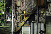 side view of a building with stairs and gas bottles during night