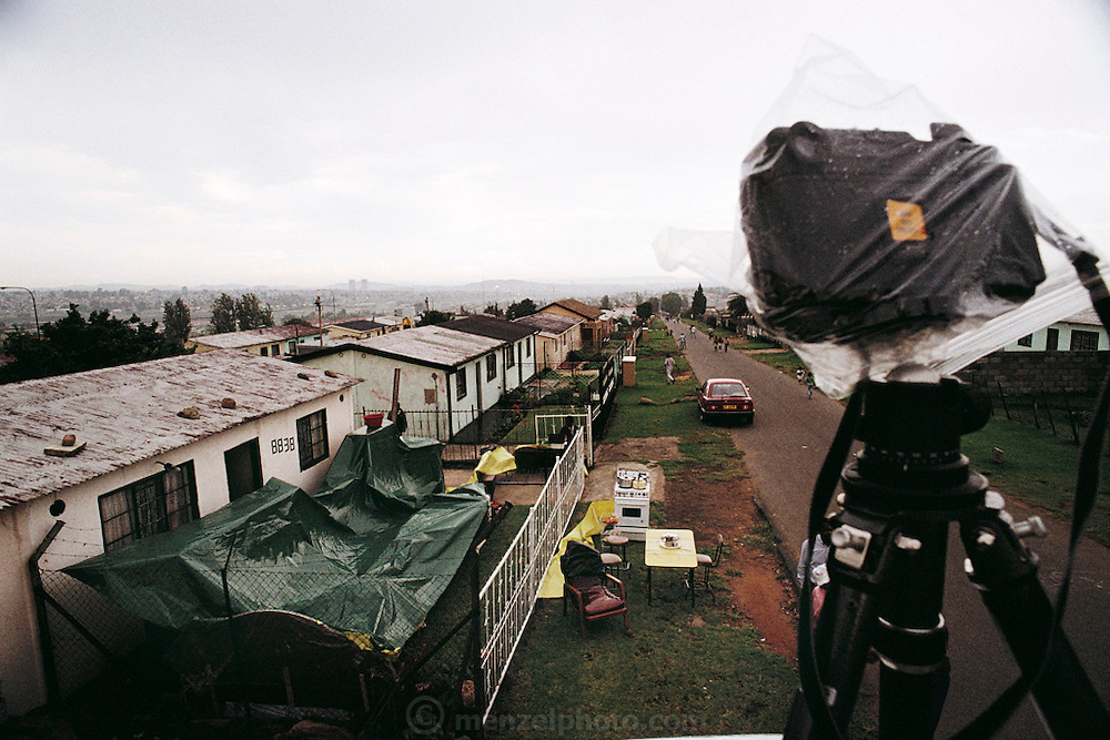 Rain delay during the shooting of the Material World big picture in South Africa. The Qampie family had to cover all their possessions, which had already been moved outside, during the brief but fierce thunderstorm that swept across Soweto. The Qampie family lives in a 400 square foot concrete block duplex house in the sprawling area of Southwest Township (called Soweto), outside Johannesburg (Joberg) South Africa. Material World Project.