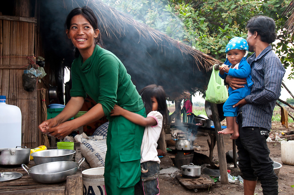 "Sokhon prepares dinner with her daughter Sreymao by her side.  Sokhon's husband, Khhuan Ry, holds another family member behind her...Arriving at home near sunset Sokhon's daughter Sreymao, age 7, runs out the greet her.  Sokhon sits down in front of her parent's house - a bamboo hut with a sheet metal roof, measuring 5 meters by 4 meters.  Inside electricity comes from a car battery that powers one 12 watt light bulb and a small TV.  Next door Sokhon's house has a palm leave roof measuring 3 meters by 3 meters. She shares it with Sreymao.  Sokhon changes her black work boots for pink slippers.  She pauses to put Sreymao's hair in a ponytail and begins cooking for her family...Sokhon's mother (need her name?) sits down outside, she says, ""We are so proud of her!""  She admits Sokhon is the primary reason the family is slowly escaping poverty and paying for her daughter and siblings to attend school.  With Sokhon's help they recently purchased a small plot of farmland where they plan to build a house...The last light of day trickles in over the Cardomon Mountains highlighting Sokhon's smile.  She sits down with Sreymao who is busy studying her 2nd grade schoolwork.  Sokhon says, ""I want her to be a doctor, but we are too poor for that.  I hope she can be a nurse.""..Standing behind them, far enough away that he can't hear is, (need name), Sokhon's new husband.  Sokhon says:  ""My husband gives me good support. I cannot find another man better than him.  He doesn't drink and helps with the house work.  He carries water from the river.  He is responsible and takes Sreymao to school.  All my hope came back to me.  So I opened my heart back up.  Yes - I am in love"".   ."