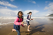 Best friends Vira Halim-Rotinsulu (left) and Isabel Durham, both nine years old, run on the beach at the Oregon Coast. (Fully released - 111106)