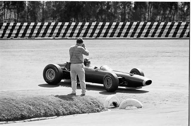 Photographer Pete Lyons gets up close and personal with BRM driver Graham Hill at the hairpin, 1965 Mexican Grand Prix
