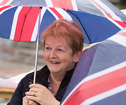 Trafalgar Square, London, June 12th 2016. Rain greets Londoners and visitors to the capital's Trafalgar Square as the Mayor hosts a Patron's Lunch in celebration of The Queen's 90th birthday. PICTURED: Not allowing the rain to dampen her spirits a woman watches the performance on the big screen.