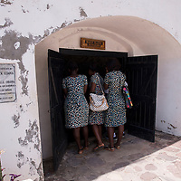 Three women in matching dresses stand at the entrance of the male slave dungeon at Cape Coast Castle, a UNESCO World Heritage Site located along the Gold Coast of Ghana.