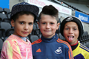 Three young Swansea fans awaiting kick off at the Capital One Cup match between Swansea City and York City at the Liberty Stadium, Swansea, Wales on 25 August 2015. Photo by Simon Davies.