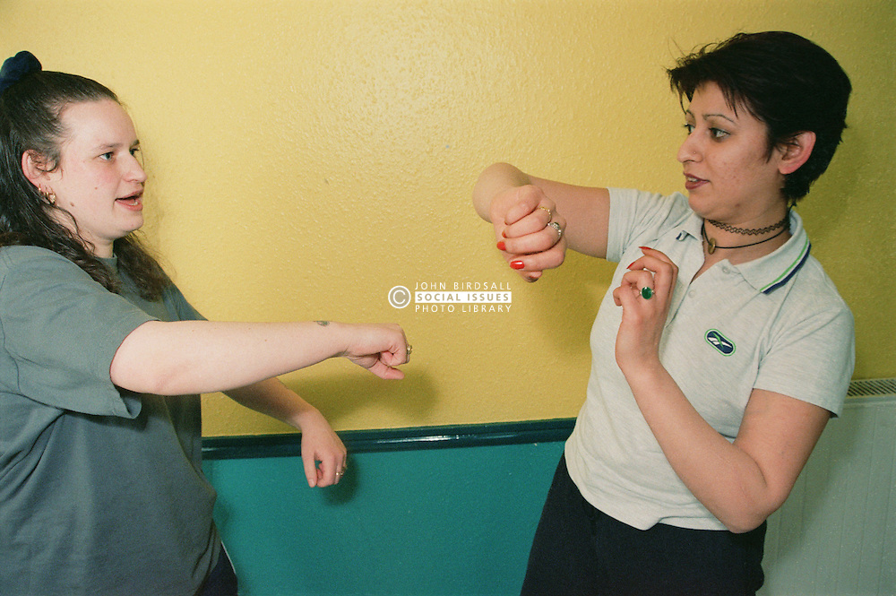 Two women practising self defence moves during self defence lesson in women only homeless hostel,