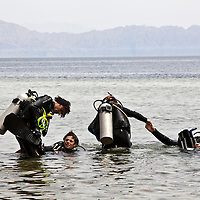 "Divers struggle as they exit the Blue Hole in Dahab, Egypt. The Blue Hole is notorious for the number of diving fatalities which have occurred there, earning it the sobriquet ""World's Most Dangerous Dive Site"" and the nickname ""Diver's Cemetery"". The site is signposted by a sign that says ""Blue hole: Easy entry"". Accidents are frequently caused when divers attempt to find the tunnel through the reef (known as ""The Arch"") connecting the Blue Hole and open water at about 52 m depth. According to dive experts roughly 10 people die each year. April 2012."