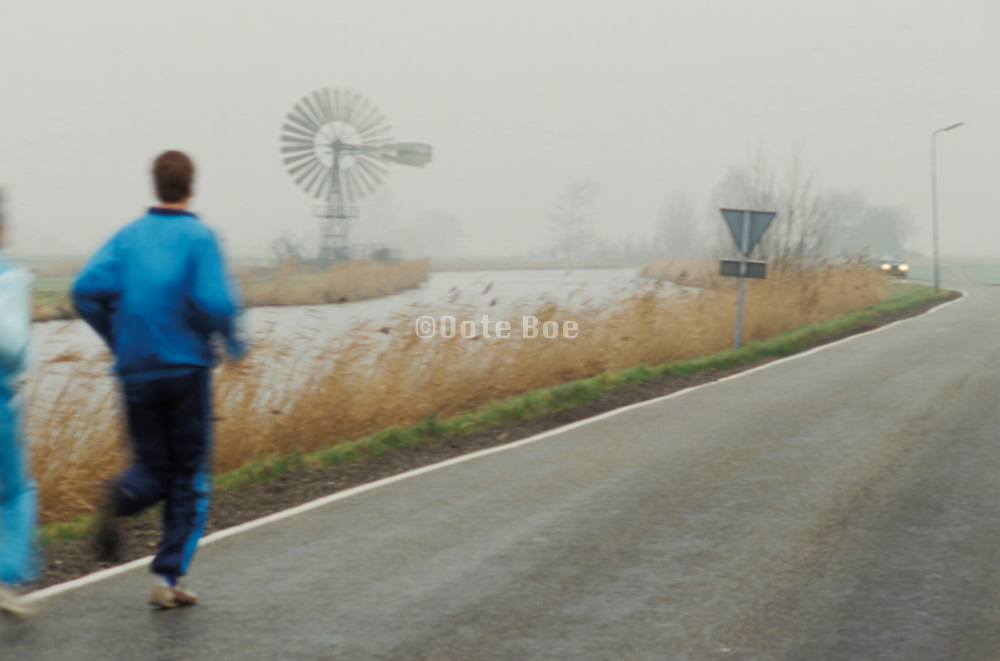 joggers on the highway by a watermill