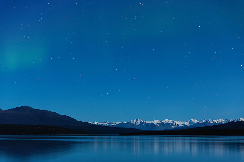 Aurora Borealis above the Alaska Range mountains at Paxson Lake in Southcentral Alaska. Autumn. Morning.