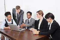 Multiethnic professionals using laptop at conference room