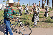 """24 MARCH 2004 - PHOENIX, AZ, USA: A pedestrian walks past the Maricopa County Juvenile Chain Gang cleaning up a vacant lot at a worksite in Phoenix, AZ, March 24, 2004. The juveniles volunteer to serve Maricpoa County Sheriff Joe Arpaio's chain gang. The sheriff, who claims to be """"the toughest sheriff in America,"""" has chain gangs in both the men's and women's jails and now has a chain gang for juveniles sentenced and serving time as adults in the county jail system. The sheriff claims it is the only juvenile chain gang in the country.   PHOTO BY JACK KURTZ"""