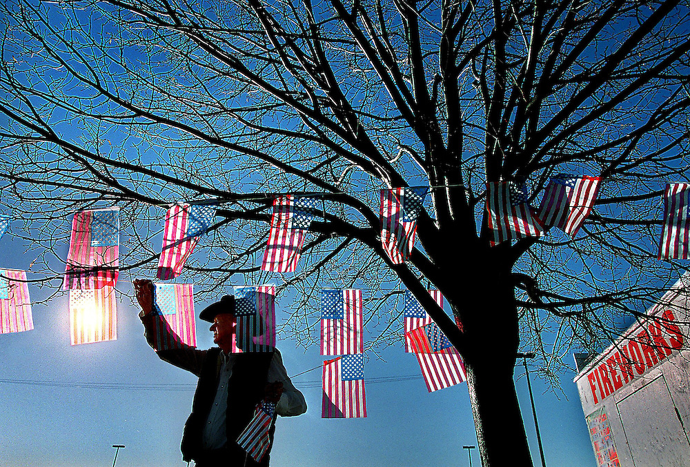 Setting up in the morning at his families firework stand Marion Richardson 74, from West Sacramento puts up  a string full of American flags. The stand was to support Job's Daughter Bethel 338. PIcture was taken at El Camion Ave. near Fulton.
