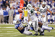Mark Sanchez of the New York Jets tries to throw a pass while being pressured by Eric Foster (68) and Robert Mathis (98) of the Indianapolis Colts during the AFC Wild Card Playoff game at Lucas Oil Stadium on Jan. 8, 2011 in Indianapolis, IN.