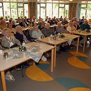 Mw. v/d Kamp Vooranker overhandigd 1ste euro aan bewoner, oude bewoners luisteren
