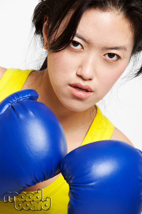 Portrait of serious Asian woman wearing boxing gloves against white background