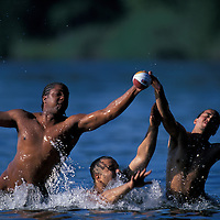 USA, Washington, Seattle, Young men play football in Lake Washington in Seward Park on summer afternoon