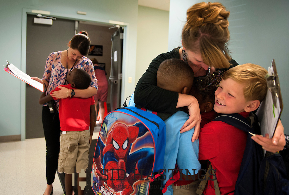 12 AUG. 2015 -- ST. LOUIS -- Amy Hertert (center right), a first grade teacher at Lafayette Preparatory Academy in St. Louis, is hugged by LPA second grade students Victor Colzie (center left) and Harlan Sigler (right) while first grade teacher Emily Robertson (left) greets second grader Malaiki Gayfield before classes start on the first day of the 2015-16 school year at the academy in downtown St. Louis Wednesday, Aug. 12, 2105. The children had Hertert and Robertson as their first grade teachers last school year.  Photo © copyright 2015 Sid Hastings.