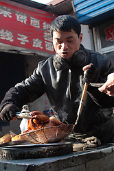 China, Taiyuan, 2005. Freshly-cooked chickens are available daily in Jian Cao Ping's local market, courtesy of the vendors who work here most of the day..