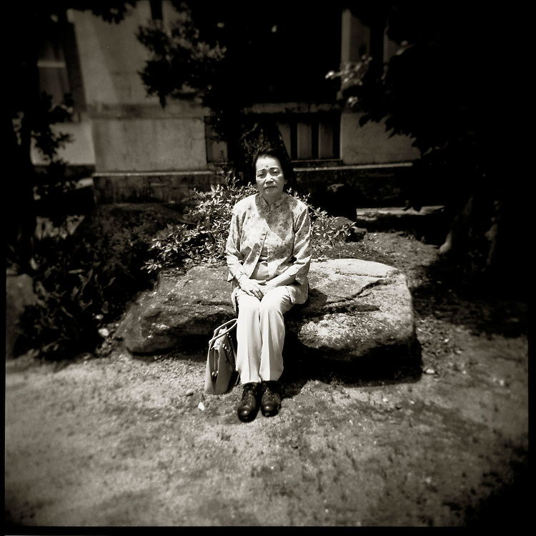 Ms. Etsuko Nagano 76 Sits on a  rock near the building she was in whil working at a  local Highschool on Aug. 6 1945.