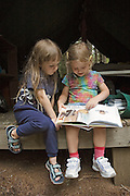 2 4 year old girls reading a book together at summer camp