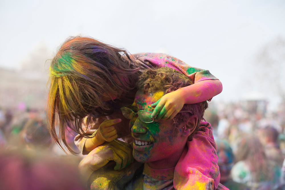 After a young girl throws green powder in his dads face, she realizes its in his eyes and tries to help him while he remains smiling and in good sprits at the Holi Festival of Colors, on Saturday, Mar. 24, 2012, at the Lotus Temple, in Spanish Fork, Utah. (Photo by Benjamin B. Morris ©2012)