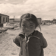 A young Tibetan girl looks shyly at the camera in the village of Tingri, Tibet, China.