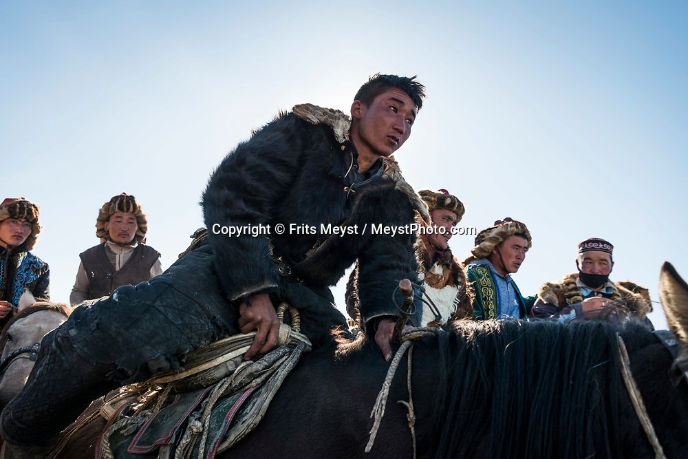 "Ulgii, Altai Mountains, Mongolia, September 2017. Buzkashi (literally ""goat pulling"" in Persian), is the Central Asian sport in which horse-mounted players attempt to place a goat or calf carcass in a goal. It is played predominantly by Turkic people. It is not uncommon for fights to break out during the battle, which can be best decribed as a tug of war'. Ethnic Kazakh horsemen from all over the Altai mountains gather in a dusty valley for the annual Altai Golden Eagle Festival. At this two day event, they compete in centuries old Eagle hunting skills, marksmanship and horsemanship. Nowadays, small groups of tourists attend the festival, but in no way is this a tourism event.  Photo by Frits Meyst / MeystPhoto.com"