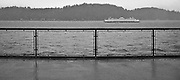A Washington State Ferry passes in Rich Passage of Puget Sound on a rainy day. The panoramic view is from behind a railing on another ferry. The image is black and white and reticulated in texture. WA, USA