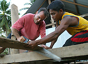 Koh Lanta, Thailand--David Karam (left), of Brewster, MA, helps Taluk Khlongdee build a deck for his new home after the Tsunami destroyed it December 26th in the village of Hua Laem on Koh Lanta island, Thailand.  Khlongdee's was just one of many homes destroyed in the village. Karam was on his way to Southeast Asia when the Tsunami hit and headed to Koh Lanta to see how he could help.  01/25/05 © Julia Cumes / The Image Works
