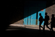 Three silhouettes walk into shadows beneath south London railway tunnel.