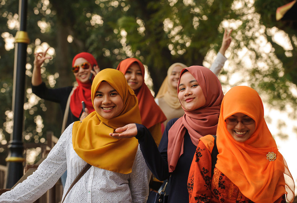 Young Malaysian women in traditional headscarves pose for the camera in Malacca, Malaysia.