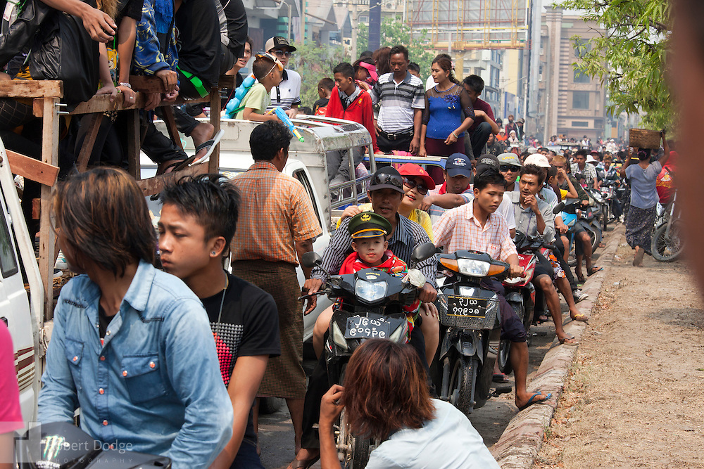 andalay, Myanmar- April 14, 2013: Motorists jockey for the best position to navigate the traffic jams during Myanmar's Thingyan Water Festival. Thingyan is held in April, one of the hottest months of the year in Myanmar. The water festival marks the country's New Year celebration and the festival includes lots of drinking, singing, dancing and theater. Wherever you are you are likely to get doused with water as the Burmese see this as a cleansing of the previous year's sins and bad luck and a blessing for good luck and prosperity in the year ahead. In the major cities of Mandalay and Yangon, large platforms are erected along major roadways and are equipped with high powered water hoses. The platforms, sponsored by large corporate donors, also have dance stages and play the latest pop and hip hop music. Thousands of residents pour into the streets by foot, motorbike and flatbed truck to get hosed under the platforms while they drink and dance. Many of the young celebrants wear their best clubbing clothes. And many of the party goers are men, having left their wives and girlfriends at home.