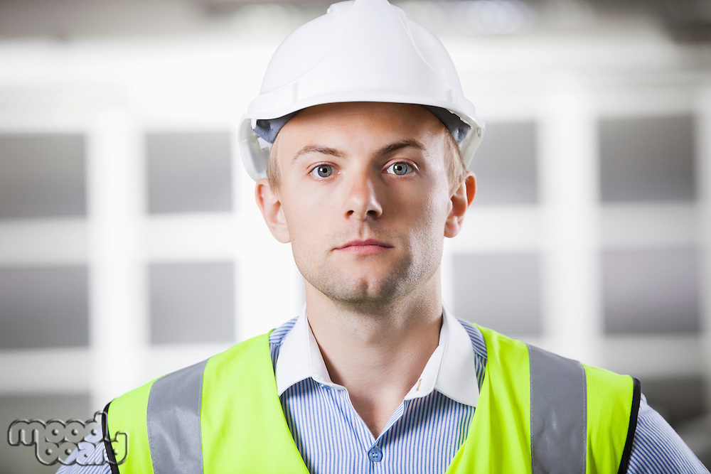 Portrait of confident young architect in hard hat and safety vest