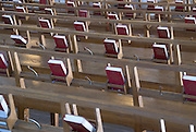 Copies of the Swedish Psalm Book sit in holders along the backs of the wooden benches in the Holy Cross Chapel at Skogskyrkogården, Stockholm, Sweden