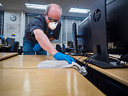"19 MARCH 2020 - DES MOINES, IOWA:  HOWARD HENRY, a worker for the Des Moines Public Schools, cleans a computer arts classroom at Central Campus, a high school in the Des Moines Public Schools system. Des Moines schools are closed for at least 30 days because of the coronavirus and officials are using the time to ""deep clean"" and sanitize each school. On Thursday morning, 19 March, Iowa reported 38 confirmed cases of the Coronavirus. Restaurants, bars, movie theaters, places that draw crowds are closed for at least 30 days. There are no ""shelter in place"" orders in effect anywhere in Iowa but people are being encouraged to practice ""social distancing"" and many businesses are requiring or encouraging employees to telecommute.      PHOTO BY JACK KURTZ"