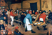 The Peastant Wedding' Musicians centre left, playing bagpipes. Guests are feasting and drinking. Platters of food are being distrubted by two men with a tray of planks.  The bride, wearing a crown and with hair flowing free, sits in front of blue hanging.  Pieter Brueghel the Elder (c1525-1569) Netherlandish Renaissance painter