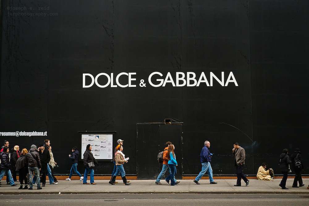 People walking past storefront under construction with large Dolce & Gabbana sign on Fifth Avenue, New York, NY