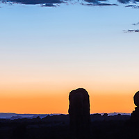 Crescent moon setting beyond Balanced Rock in Arches National Park
