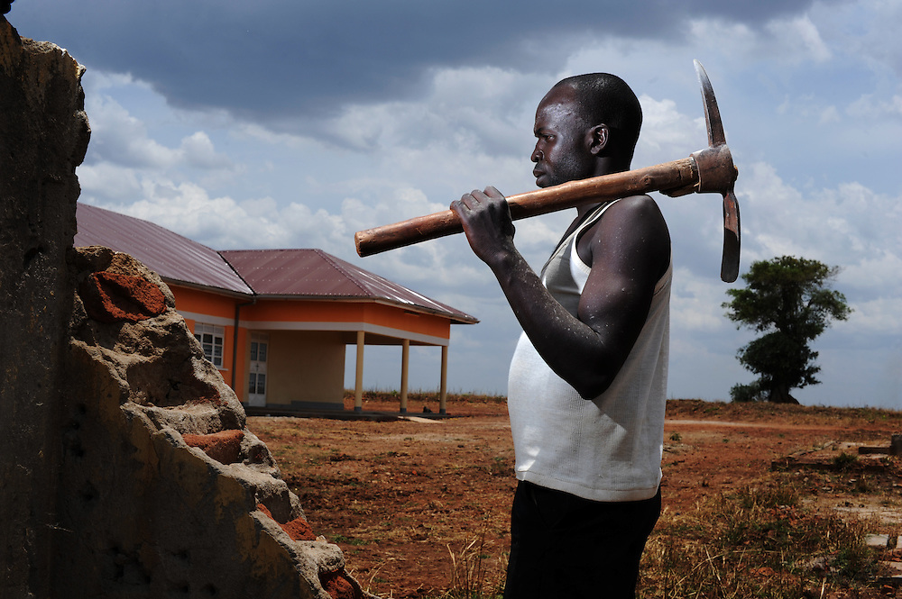 12-03-26   -- LIRA, UGANDA -- Worker Geoffry Odongo clears the site of the Bala Stock Farm IDP camp, making way for the new Gulu University satellite campus near Lira, on March 26.  Locals say nearly 40,000 people stayed on the hilltop property. Currently, ten still remain and will be evicted as others have, say university officials.  Photo by Daniel Hayduk