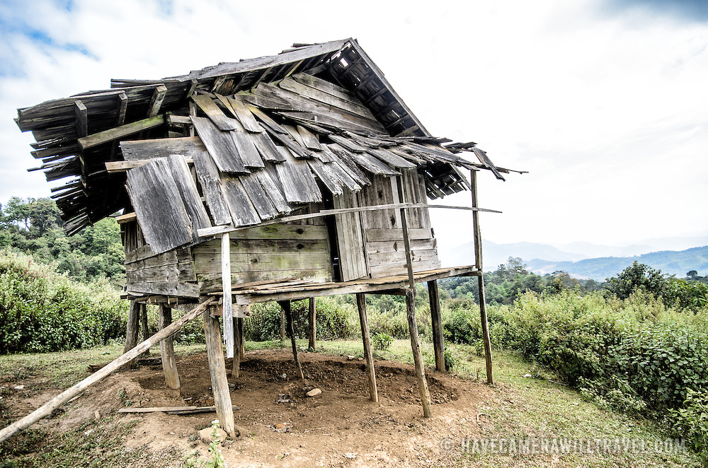 A ramshackle wooden rice storage hut sits on stilts in northern Laos.