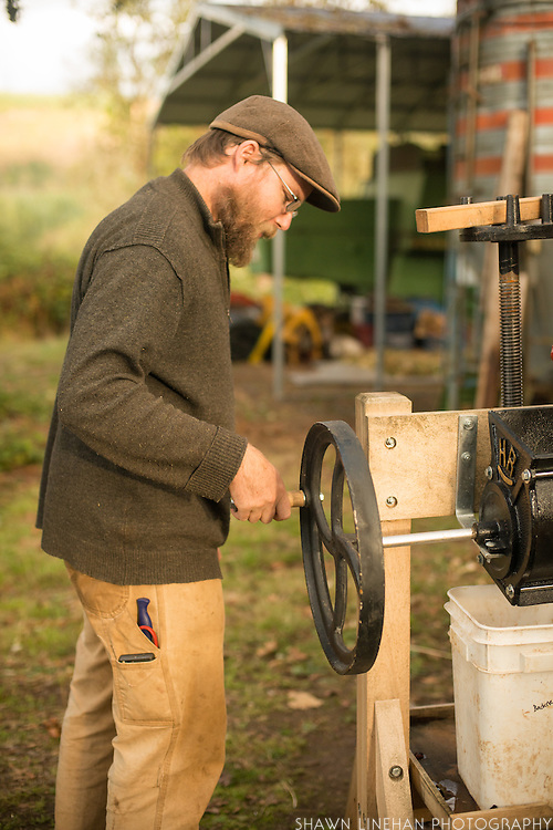 Andrew Still of Adaptive Seeds in Sweet Home, OR uses an apple press to grind up peppers to save seed.