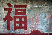 "The Chinese character ""Fu"" meaning happiness is painted on a wall of a hutong in Beijing."