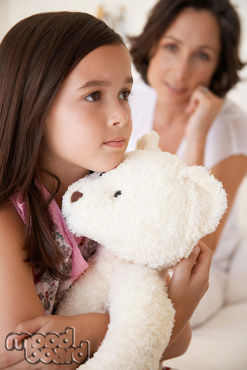 Girl hugging teddy bear half length mother in background