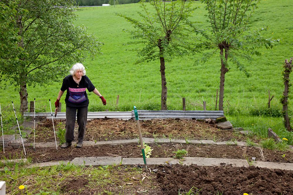 The Glad Ostensen family in Gjerdrum, Norway. Anders Ostensen's mother works in her garden behind the farmhouse.