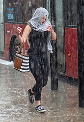 © Licensed to London News Pictures. 10/08/2018. London, UK. A woman covers her head with a sweatshirt as she runs for cover during a sudden rain shower in Uxbridge. Photo credit: Peter Macdiarmid/LNP