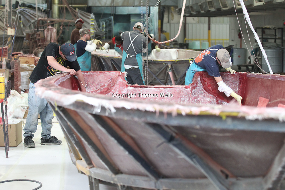 Workers begin spreading and gluing fiberglass into molds to form the hull of boat.