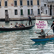 "VENICE, ITALY - JANUARY 16:  A protester sailing on the Grand Canal holds black listed banner reading ""Stop the large Ships""  on the day of the special meeting discussing the environmental impact of cruises in Venice on January 16, 2012 in Venice, Italy. Protest are mounting in Venice against large cruise ships crossing St Marks's basin after the Costa Concordia tragedy.."