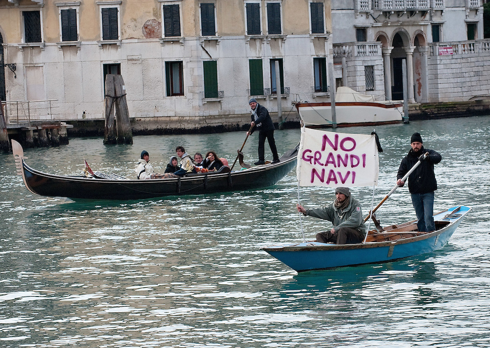 """VENICE, ITALY - JANUARY 16:  A protester sailing on the Grand Canal holds black listed banner reading """"Stop the large Ships""""  on the day of the special meeting discussing the environmental impact of cruises in Venice on January 16, 2012 in Venice, Italy. Protest are mounting in Venice against large cruise ships crossing St Marks's basin after the Costa Concordia tragedy.."""