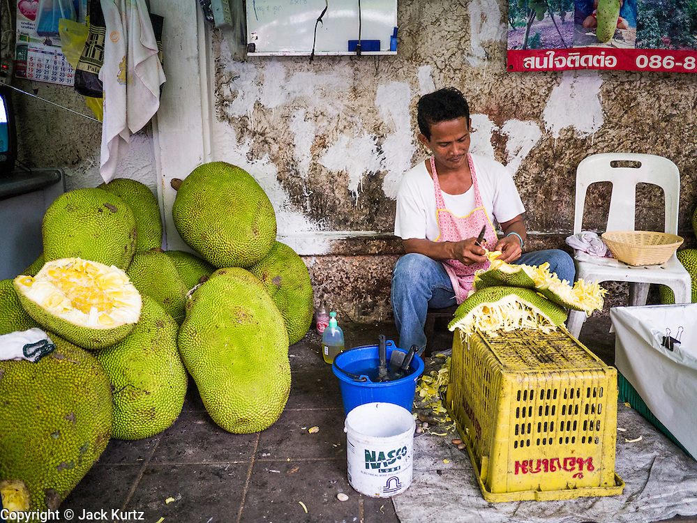 30 MAY 2013 - BANGKOK, THAILAND:   A man cuts up durian fruit before selling it near Bobae Market in Bangkok. Bobae Market is a 30 year old famous for fashion wholesale and is now very popular with exporters from around the world. Bobae Tower is next to the market and  advertises itself as having 1,300 stalls under one roof and claims to be the largest garment wholesale center in Thailand.   PHOTO BY JACK KURTZ